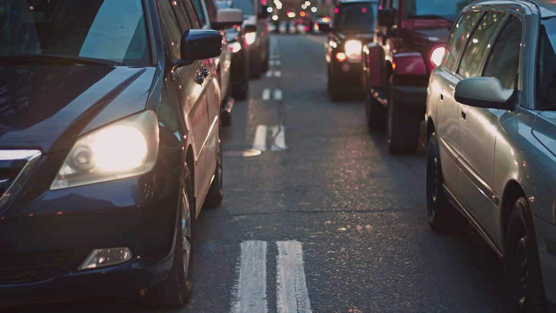 Via urbana con coches estacionados y parados