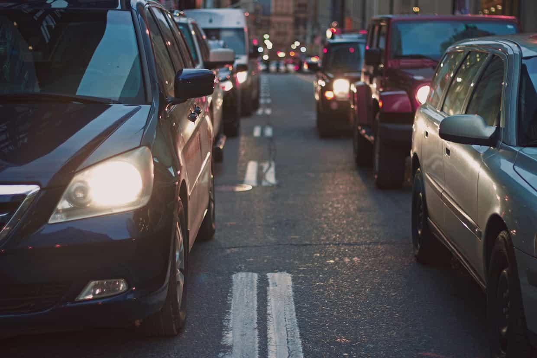 Vía urbana con coches estacionados y parados.