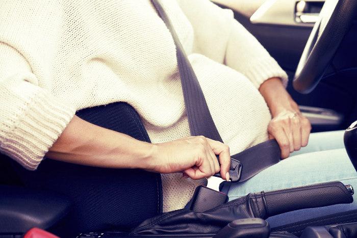 Mujer embarazada colocándose el cinturón de seguridad