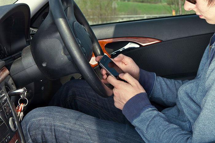 Conductor novel distraído con el móvil